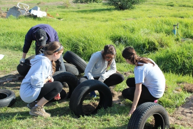 Evan, Chrystal, Larisa, & Emily putting the tire obstacles into the playground.