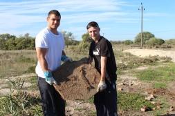 Ryan & Vinny holding up a piece of concrete found underground.