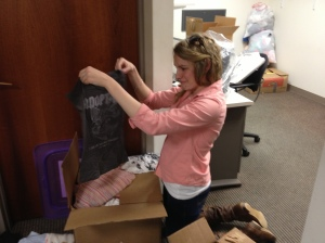 Alison folding shirt to pack for Tippy Toes communities in South Africa.