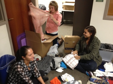 Adriana, Alison, & Libby folding and organizing donations.
