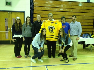 The class posing with the winner of the Frozen Four Hockey Jersey and QU Men's Ice Hockey Coach Rand Pecknold.