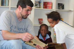 Peter reading a book to children.