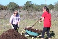 Kristyn & Melanie shoveling compost at Varkplaas garden.