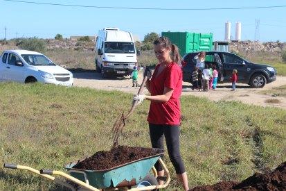 Melanie shoveling compost at Varkplaas garden.
