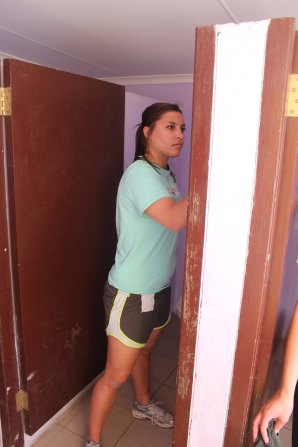 Libby painting the inside of the girls' bathroom at the Vaatjie Primary School.
