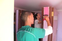 Jason & Tamarin painting the inside of the girls' bathroom at the Vaatjie Primary School.