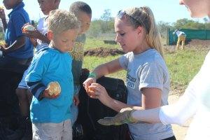 Kristyn giving oranges to kids in Varkplaas.