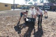 Devin, Melanie, & Jeassica watering soccer field.
