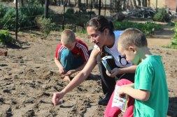 Adriana planting seeds in Vaatjie Primary School Garden with Liam & Morgan.
